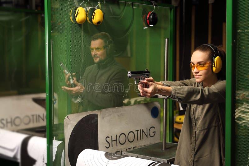 Kvinnan skjuter ett vapen på en skjutbana arkivbild