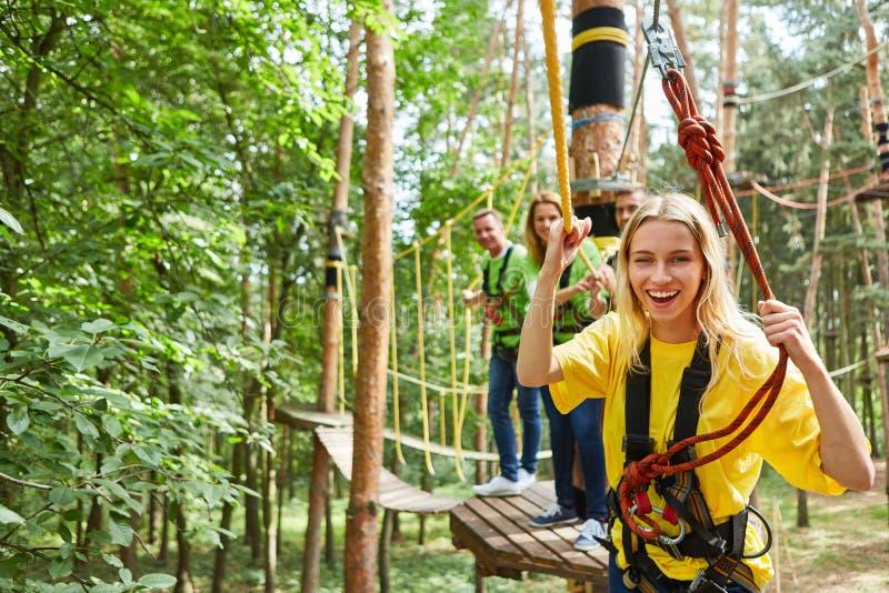Kvinnan skrattar proudly i klättraskogen på en bro arkivfoton