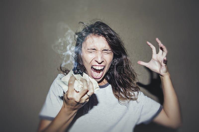 Kvinnan skriker och svär med ett tänt skrynkligt stycke av papper i a arkivbilder
