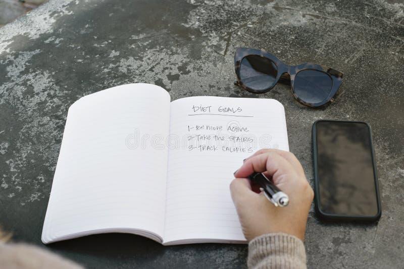 Kvinnan skriver hennes bantar mål i tidskrift arkivfoton