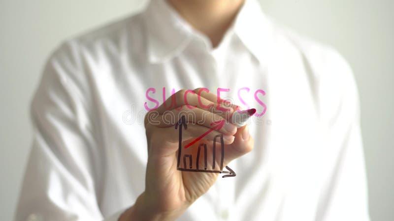 Kvinnan skriver tillväxtdiagrammet med den röda övre pilen och framgång på den genomskinliga skärmen royaltyfri fotografi