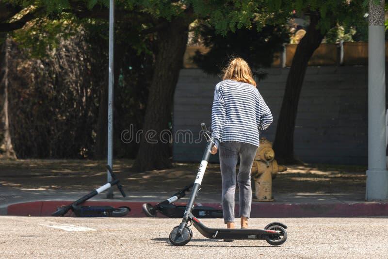 Kvinnan släpar FÅGELsparkcykeln över gatan arkivbilder