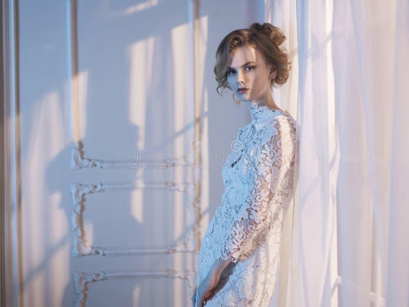Kvinnan snör åt in klänningen på fönstret royaltyfri foto