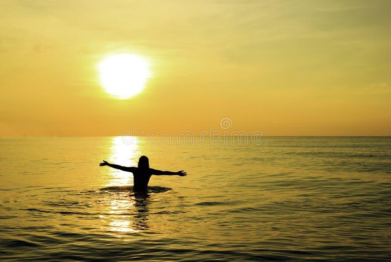 Kvinnan solbadar på soluppgång royaltyfria bilder