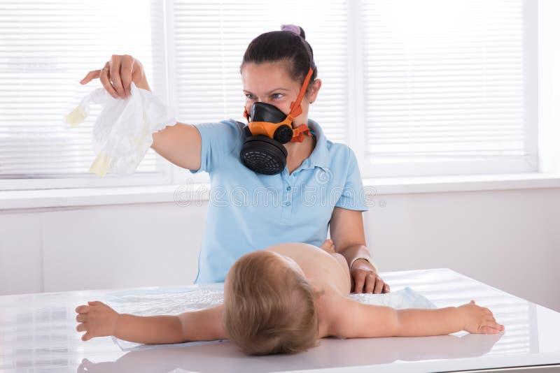 Kvinnan som ändrar den stinkande nappyen av henne, behandla som ett barn arkivbild