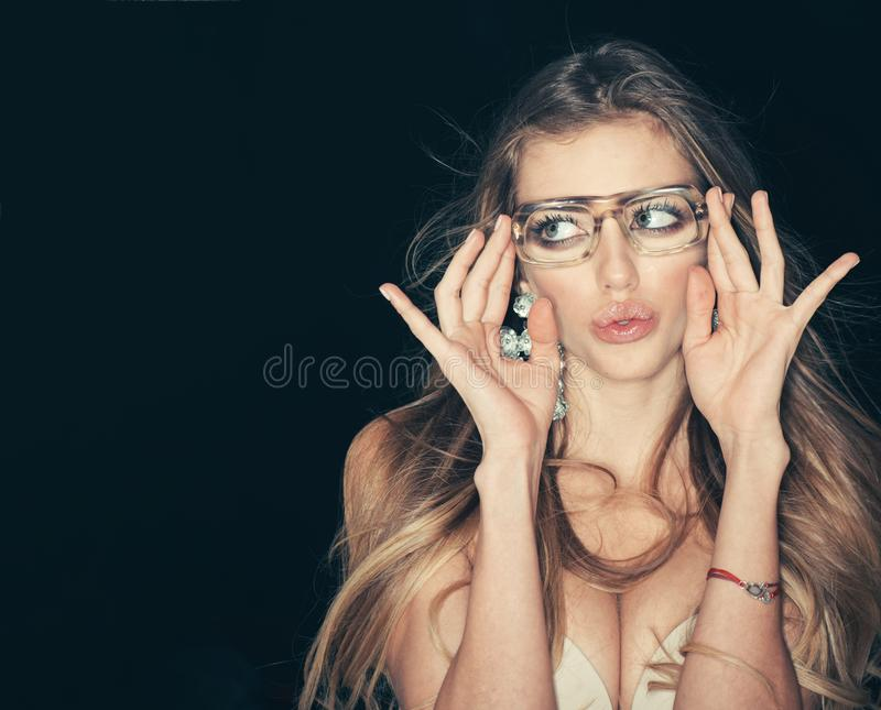 Kvinnan som är attraktiv med stora bröst, bär fult glasögon för vision Sexig flicka med makeup och stora örhängen som är mörka fotografering för bildbyråer