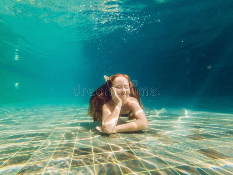 Kvinnan som är längst ner av pölen, dyker hon under vattnet arkivfoto