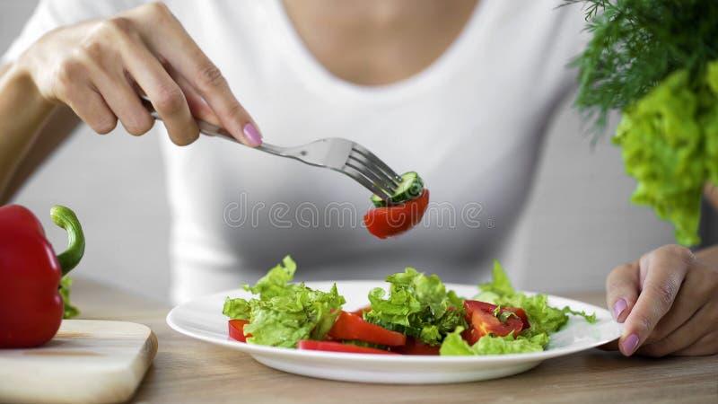 Kvinnan som äter grönsaksallad och att observera bantar och räkna kalorier, wellness arkivbild