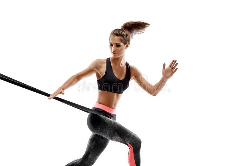 Kvinnan som övar konditionmotstånd, sätter band i studiokonturn som isoleras på vit bakgrund arkivbild
