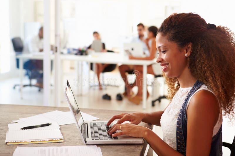 Kvinnan som använder bärbara datorn i modernt kontor av, startar upp affär royaltyfri bild