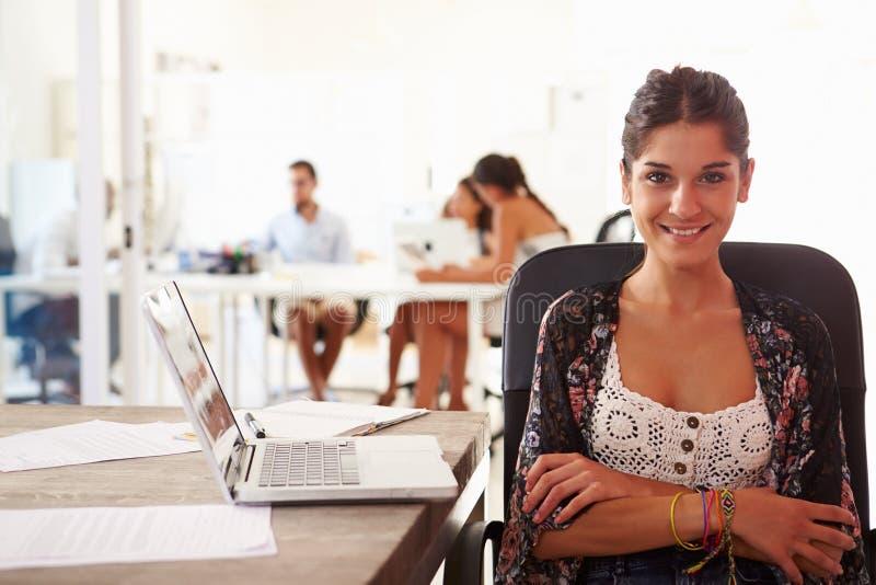 Kvinnan som använder bärbara datorn i modernt kontor av, startar upp affär fotografering för bildbyråer