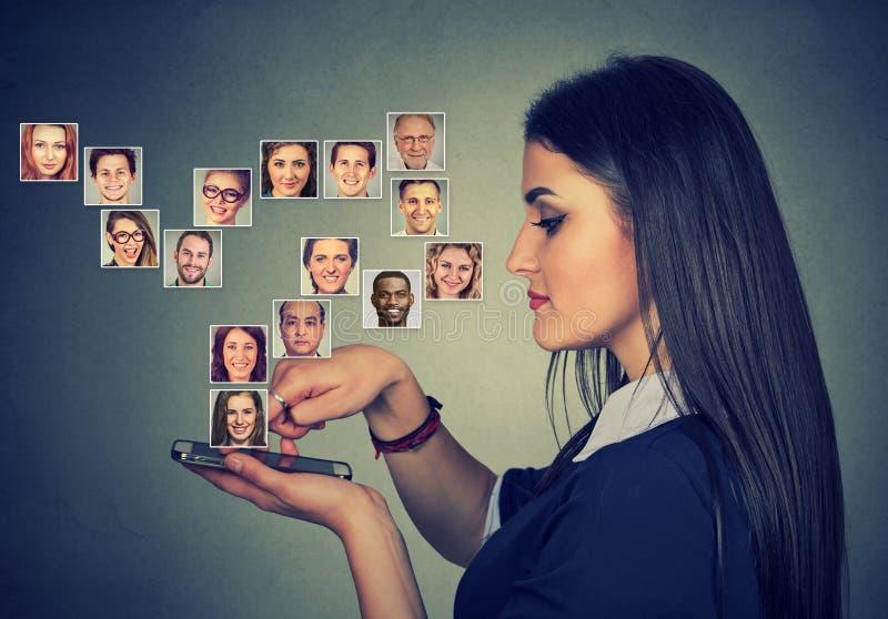 Kvinnan som använder den smarta telefonen, har många kontakter i mobil phonebook arkivbild