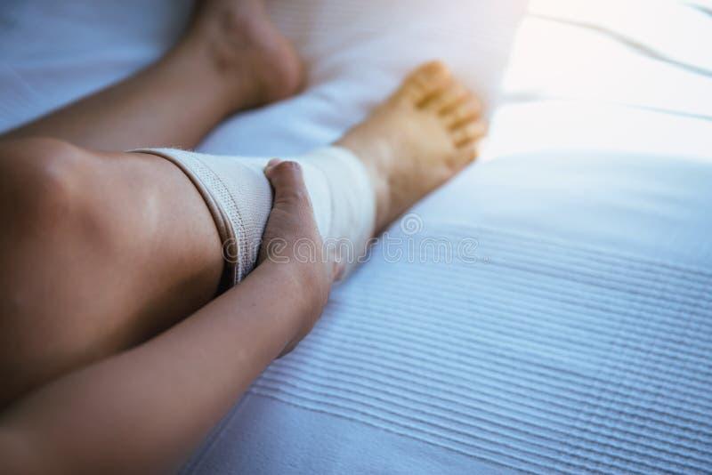 Kvinnan som använder pålagd resår, förbinder med ben som har knäet, eller benet smärtar fotografering för bildbyråer