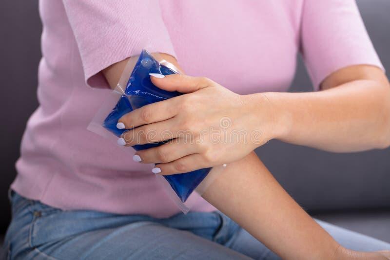 Kvinnan som anv?nder is, stelnar packen p? armen royaltyfria foton