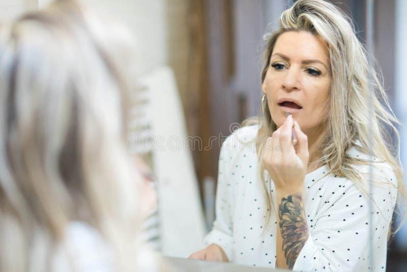 Kvinnan som applicerar morgon, utg?r i badrummets spegel fotografering för bildbyråer