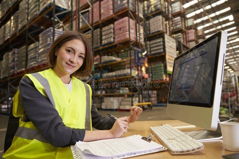 Kvinnan som arbetar i kontoret av ett lager, ser till kameran arkivfoto