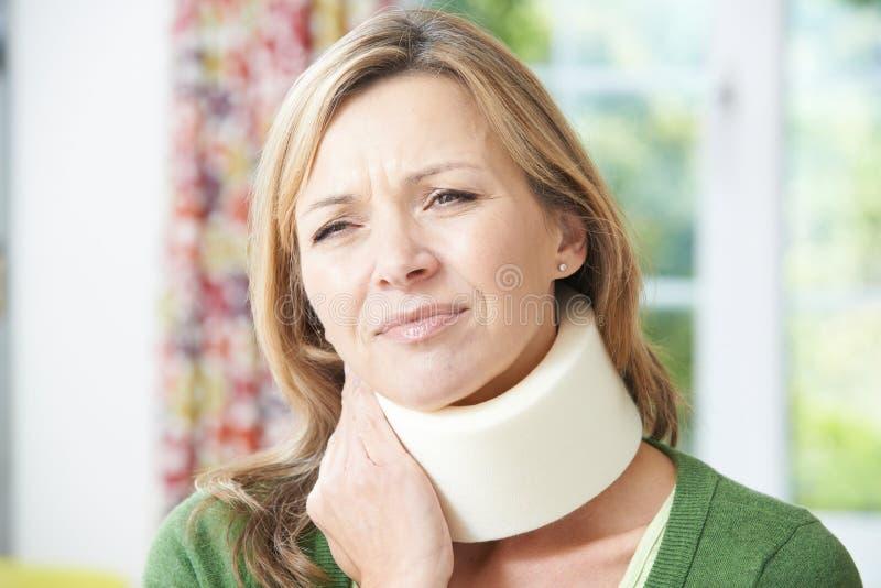 Kvinnan som bär den kirurgiska kragen smärtar in arkivfoton