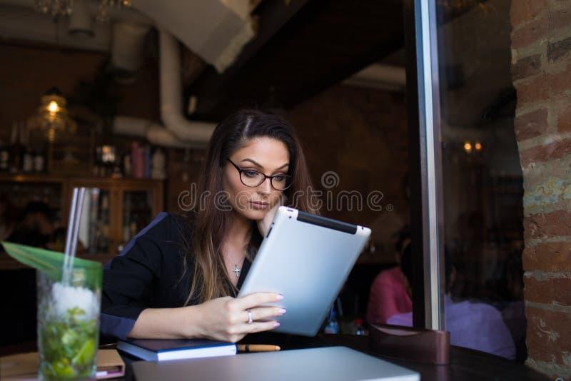 Kvinnan som bär i exponeringsglas som läser eBook på den digitala minnestavlan under, vilar i coffee shop arkivbild