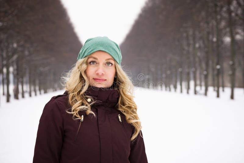 Kvinnan som bär varma vinterkläder i snö, täckte gränden royaltyfri foto