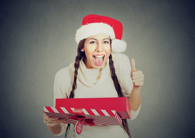 Kvinnan som bär visning för ask för gåva för Santa Claus hattöppning, tummar upp arkivfoton