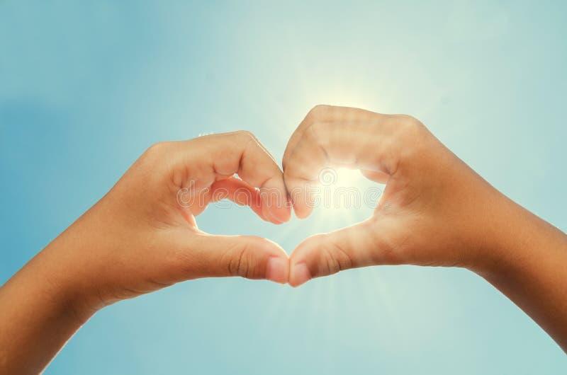 kvinnan som bildar hjärta, formade händer med backgroun för solen och för blå himmel royaltyfria foton