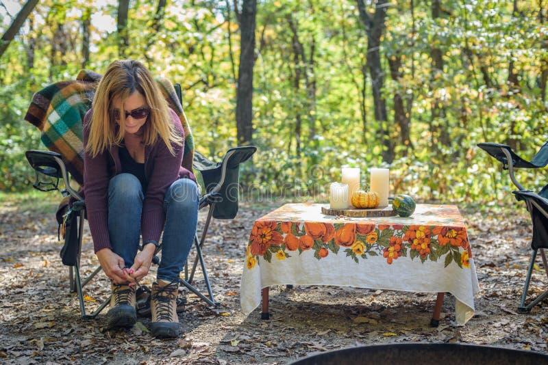 Kvinnan som binder skosnöre på att fotvandra, startar på campingplatsen royaltyfri foto