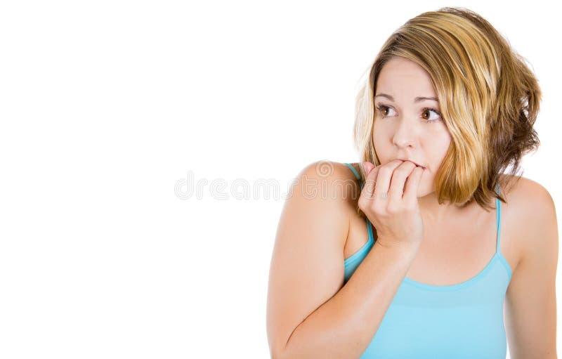 Kvinnan som biter henne, spikar och ser till sidan med ett begär för något eller angeläget arkivfoto