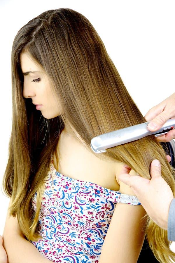Kvinnan som får mycket långt blont hår, rätade ut vid den isolerade frisören royaltyfri fotografi