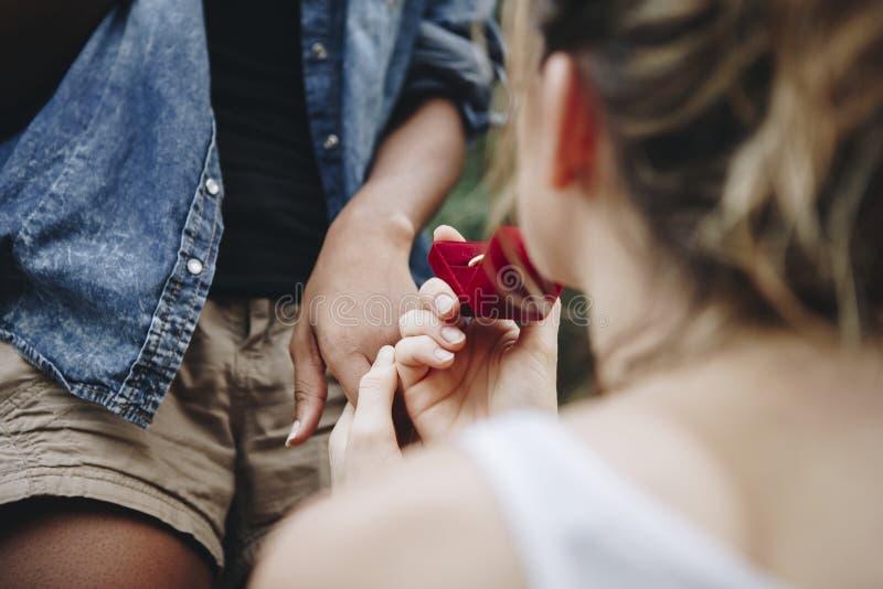 Kvinnan som föreslår till hennes lyckliga flickvän älskar utomhus, och förbindelsebegreppet arkivfoton