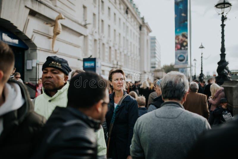 Kvinnan som går inom folkmassan över drottningen, går, i en solig dag i London, UK arkivfoto