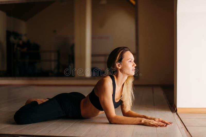 Kvinnan som gör den liggande fjärilen för yoga- eller pilatesövningen, poserar royaltyfri bild