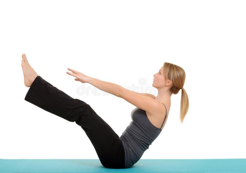 Kvinnan som gör den Pilates kuggfrågan, poserar arkivbild