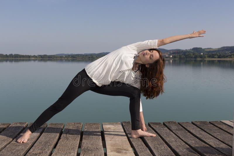 Kvinnan som gör fördjupad sidovinkel, poserar i yoga i natur royaltyfria foton