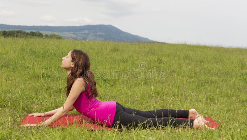 Kvinnan som gör kobran, poserar under yoga utomhus i natur royaltyfri fotografi
