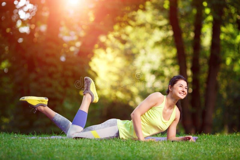 Kvinnan som gör kondition, övar i parkera arkivbild