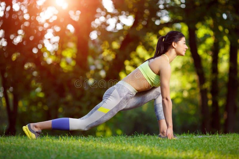 Kvinnan som gör kondition, övar i parkera royaltyfria foton