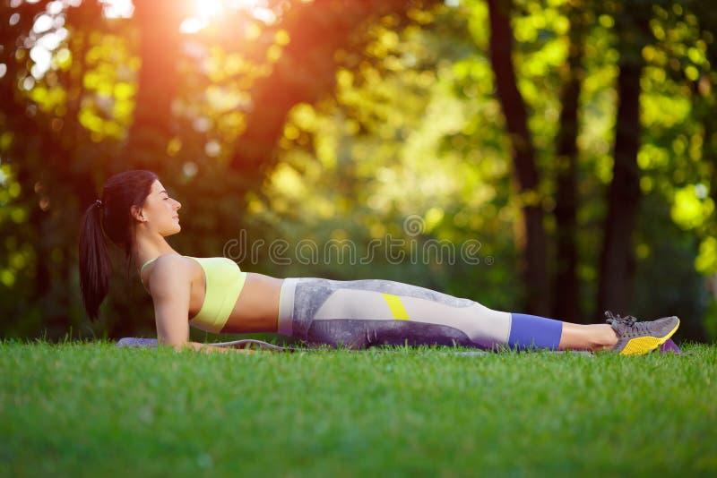 Kvinnan som gör kondition, övar i parkera royaltyfria bilder