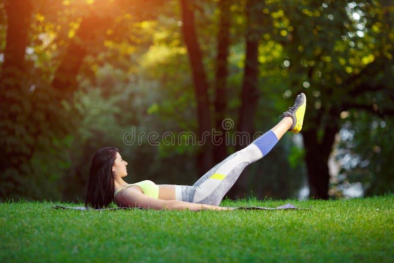 Kvinnan som gör kondition, övar i parkera royaltyfri foto