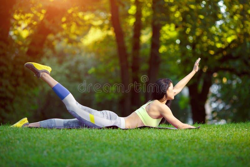 Kvinnan som gör kondition, övar i parkera arkivbilder