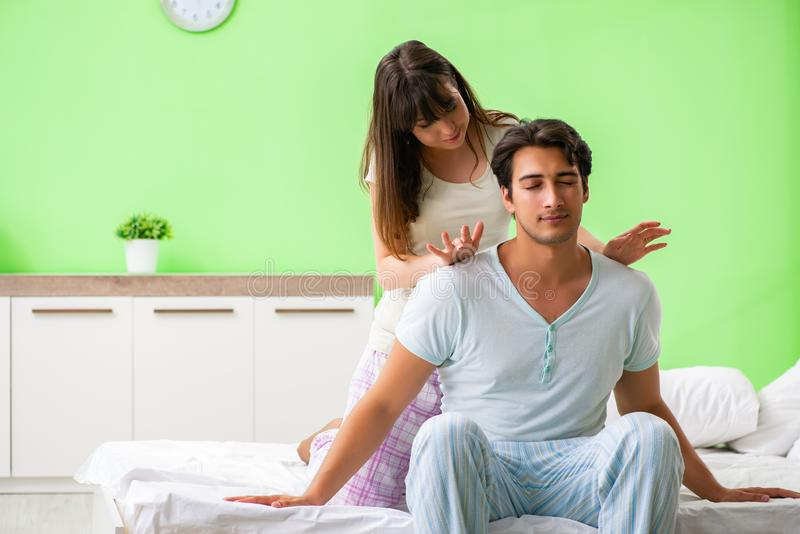 Kvinnan som gör massage till hennes make i sovrum royaltyfri fotografi