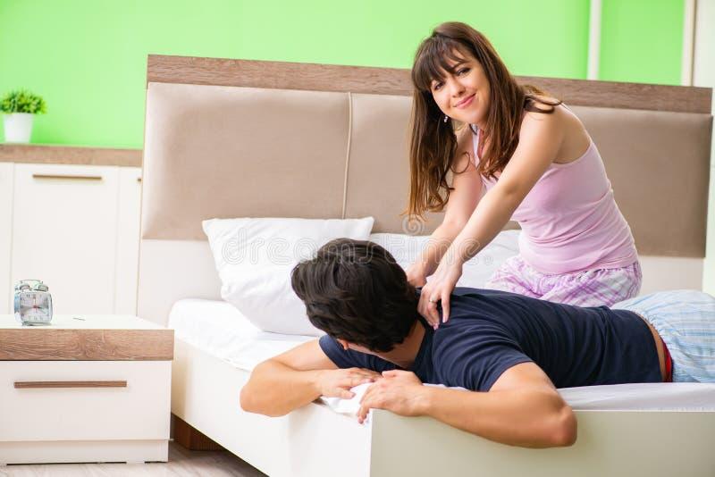 Kvinnan som gör massage till hennes make i sovrum arkivfoto