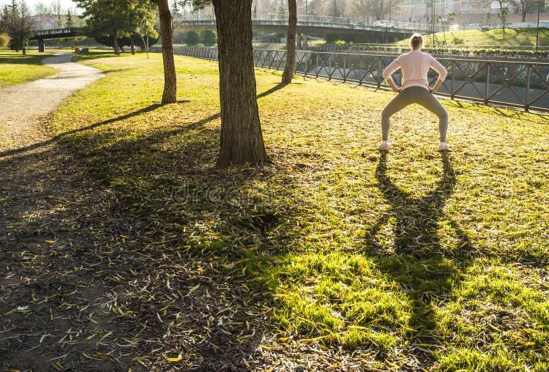 Kvinnan som gör sträcka övningar på stads-, parkerar i höstsäsong royaltyfria foton