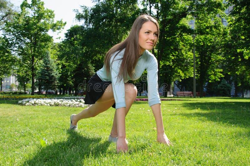 Kvinnan som gör sträckning, övar för foten utomhus i PA arkivfoton