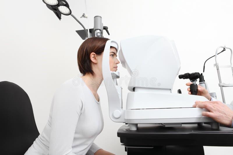 Kvinnan som gör synförmågamätning med optiker, skar upp lampan royaltyfri bild