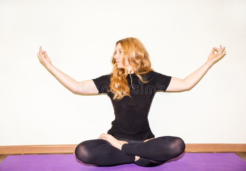 Kvinnan som gör yoga, övar, och pilates poserar på mattt på vit bakgrund Asana Begreppet av sportar, kondition, hälsa och educati arkivbilder