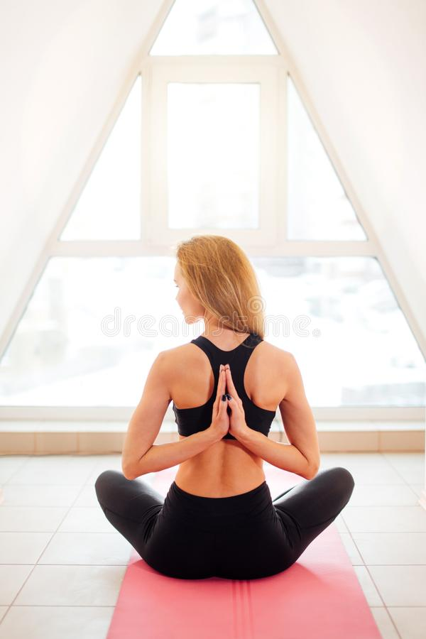 Kvinnan som gör yoga i omvänd bön, poserar Pashchima Namaskarasana arkivfoton