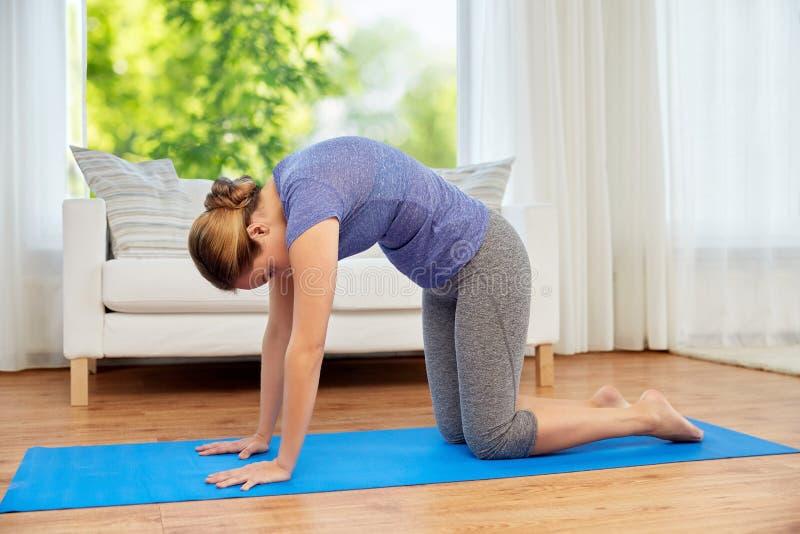 Kvinnan som gör yogakatten, poserar hemma royaltyfri bild