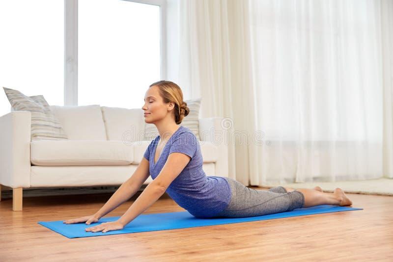 Kvinnan som gör yogakobran, poserar hemma arkivfoto