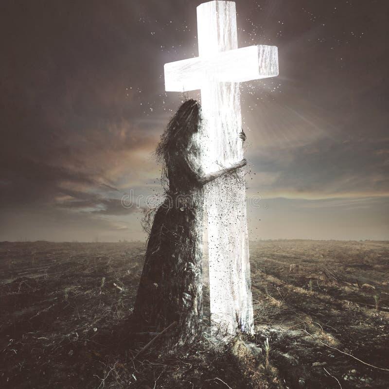 Kvinnan som göras av smuts, klamra sig fast intill korset arkivbild