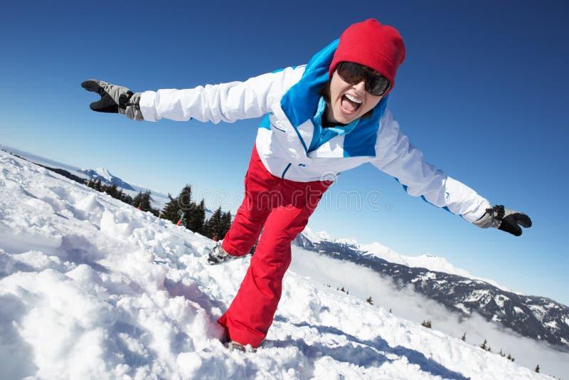 Kvinnan som har gyckel skidar på, ferie i berg royaltyfri bild
